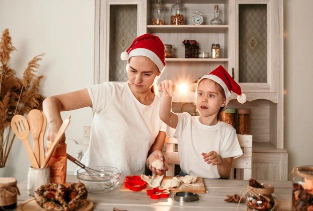 Een mooie moeder en dochter met kerstmutsen zitten aan een tafel in de keuken en maken koekjes van deeg