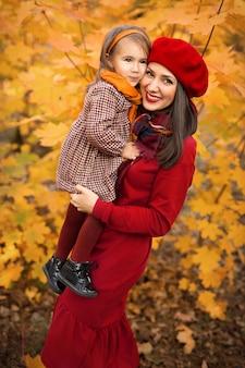 Een mooie moeder houdt haar dochtertje in haar armen op een herfstdag