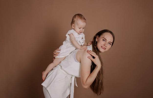 Een mooie moeder in een wit pak rijdt een meisje op haar rug op een beige achtergrond met een plek voor tekst