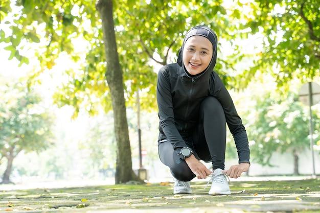 Een mooie moslimvrouwenatleet die haar schoenen binden alvorens openlucht uit te voeren
