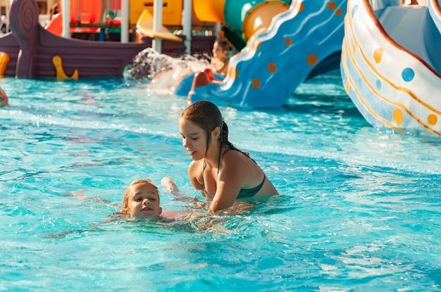 Een mooie oudere zus helpt haar jongere zusje te leren zwemmen in een zwembad met helder en transparant water