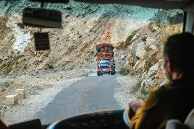 Een mooie pakistaanse versierde vrachtwagen op bergweg in karakoram-weg.