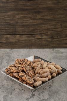 Een mooie plaat met havermoutkoekjes en noten die op een steenachtergrond worden geïsoleerd.