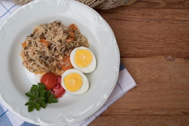 Een mooie plaat van rijst, gekookte eieren en tomaten in bovenaanzicht