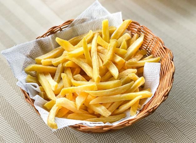 Een mooie portie frietjes in een mandje op tafel.