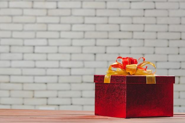 Een mooie rode geschenkdoos op een houten bord, wazige achtergrond van witte bakstenen muur, grote kopieerruimte bovenaan en links.