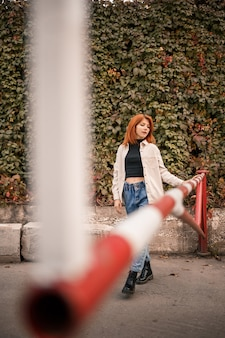 Een mooie roodharige jonge vrouw loopt over straat, ze is gekleed in een spijkerbroek en een beige shirt. mooi meisje gekleed in casual stijl met een glimlach op haar gezicht