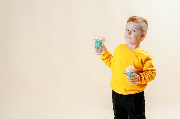 Een mooie roodharige jongen van 5 jaar in een oranje trui staat op een lichte achtergrond met ijs in zijn handen