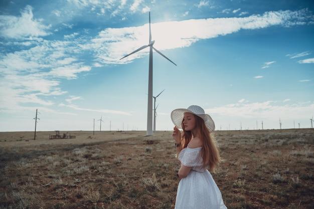 Een mooie roodharige vrouw in een witte jurk en hoed op een zinderende dag. het idee en concept van vrijheid, geluk en wildernis. vrouw voor windmolens