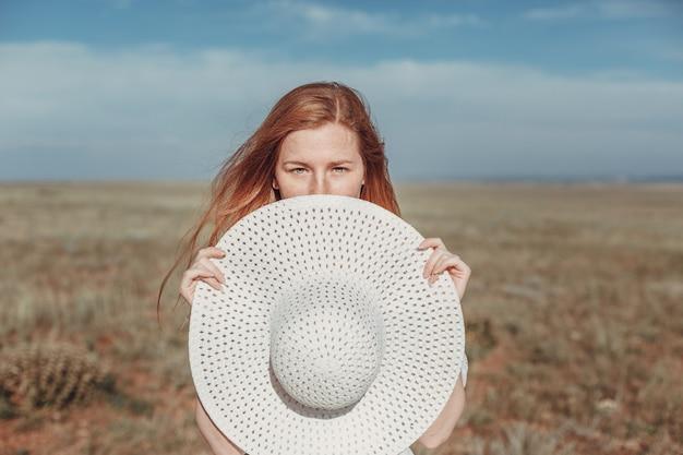 Een mooie roodharige vrouw in een witte jurk en hoed op een zinderende dag. het idee en concept van vrijheid, geluk en wildernis