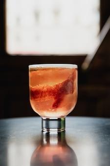 Een mooie roze cocktail met een groot ijsblokje in een lowball glas, gegarneerd met bloedsinaasappelschil