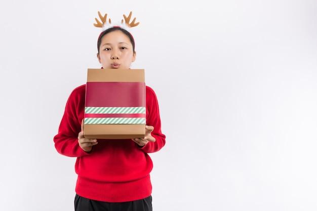 Een mooie schattige gelukkige jonge vrouw die een kerstcadeau doos opent