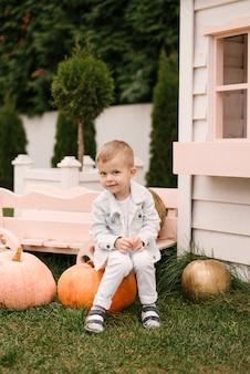 Een mooie schattige vierjarige jongen in witte kleren speelt buiten bij een wit houten huis met pompoenen