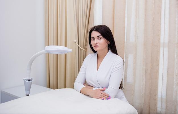 Een mooie schoonheidsspecialiste in een wit uniform zit bij de bank op kantoor couch
