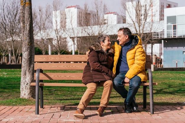 Een mooie senior paar ontspannen op een bankje in het park op een zonnige dag
