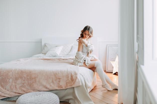 Een mooie sensuele jonge vrouw in lingerie en vest die op het bed rusten