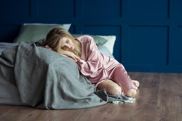 Een mooie sexy blondine met perfecte make-up en prachtig krullend rommelig haar in een roze gewaad zit op de grond bij het bed.
