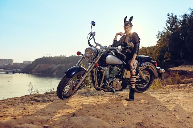Een mooie sexy jonge vrouw in leren jassen en konijnenmasker zittend op een zwarte en chromen motor.