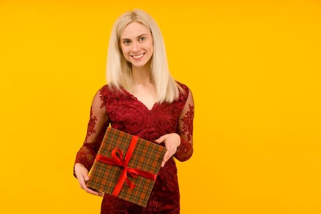 Een mooie sexy vrouw in een rode jurk houdt in handen geschenken op gele achtergrond