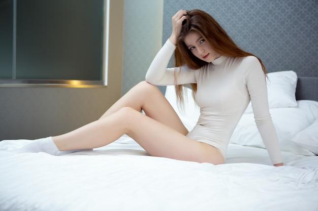 Een mooie sexy vrouw in een witte bodysuit zit op een rechtgemaakt bed