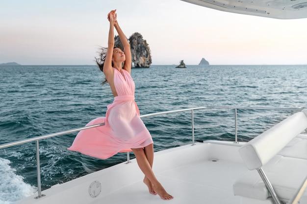 Een mooie slanke dame in een roze jurk leunt op een jacht en steekt haar handen op. geniet van de cruise. kopieer ruimte