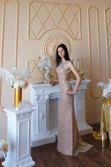 Een mooie slanke vrouw met zwart haar in een lange gouden jurk poseert in een interieur studio.