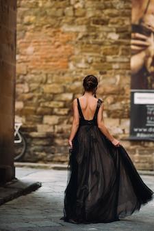 Een mooie stijlvolle bruid in een zwarte jurk loopt door florence, een model in een zwarte jurk in de oude stad van italië.
