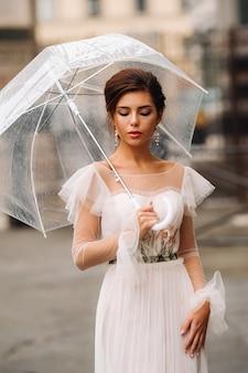 Een mooie stijlvolle bruid met een paraplu wandelt door de oude stad florence