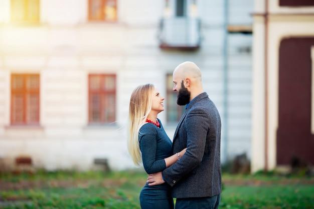 Een mooie stijlvolle emotionele paar jonge vrouw en senior man met lange zwarte baard staan dicht bij elkaar buiten in herfst straat op witte bakstenen muur achtergrond