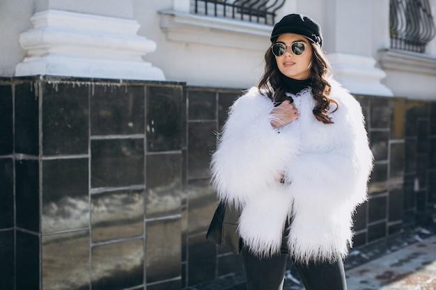 Een mooie, stijlvolle, modieuze vrouw in een bontjas, hoed en bril