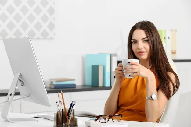 Een mooie succesvolle vrouw koffie drinken op het moderne kantoor