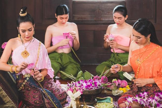 Een mooie thaise vrouw en zij draagt traditionele thaise kostuums, zowel meesters als bedienden. ze zitten bloemen te bereiden in een houten huis om verdienste te maken op de dag van de boeddha.