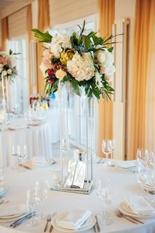 Een mooie vaas met bloemen op een tafel in een luxe restaurant.