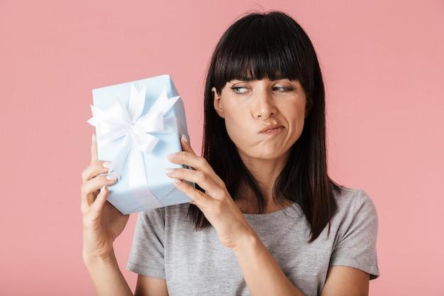 Een mooie verbazingwekkende verwarde denkende vrouw die zich voordeed over een lichtroze muurmuur met de huidige geschenkdoos.