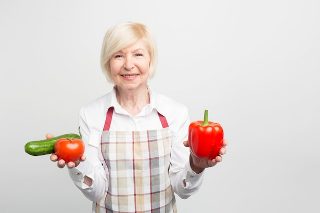 Een mooie volwassen vrouw met een rode peper in de linkerhand en zowel tomaat als komkommer in de rechterhand. ze kookt graag verschillende salades of bakt groenten.