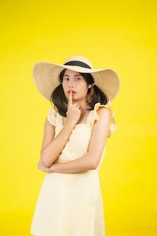 Een mooie, vrolijke jonge vrouw met een grote hoed op een geel.