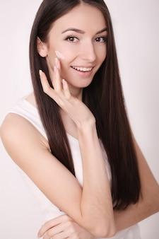 Een mooie vrouw azië met een huidverzorgingsproduct, vochtinbrengende crème of lotion en huidverzorging die haar droge teint verzorgt. hydraterende crème in vrouwelijke handen