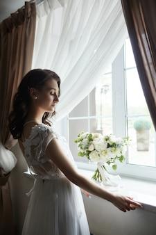 Een mooie vrouw bereidt zich voor op een bruiloft, natuurlijke make-up en een chique kapsel