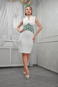 Een mooie vrouw, blond meisje in een korte witte jurk, op hakken,