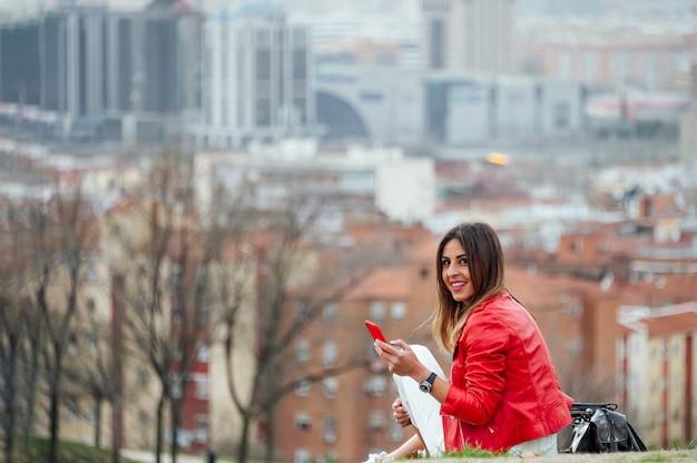 Een mooie vrouw die celtelefoon met de stad gebruikt