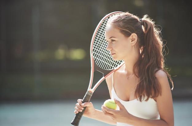 Een mooie vrouw die een bal van het sportkledingtennis draagt.