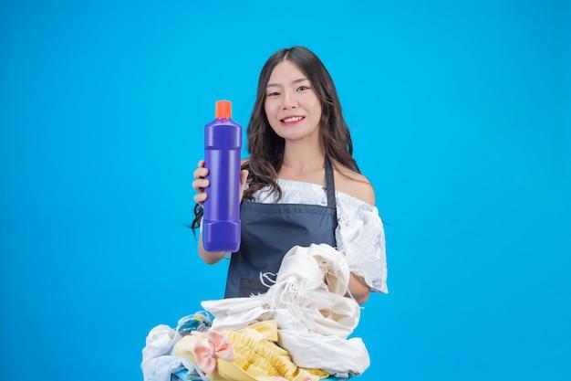 Een mooie vrouw die een doek en een vloeibaar wasmiddel houdt dat op was op blauw wordt voorbereid