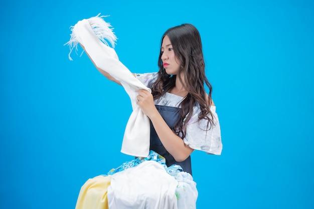 Een mooie vrouw die een doek houdt bereid om op blauw te wassen