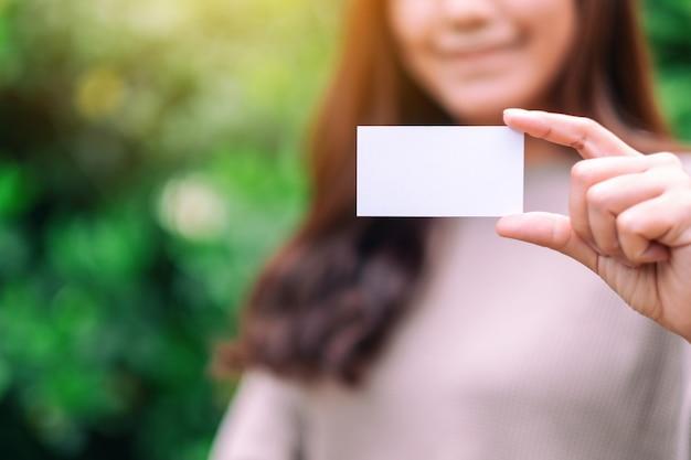 Een mooie vrouw die een leeg, leeg visitekaartje in de buitenlucht vasthoudt en toont