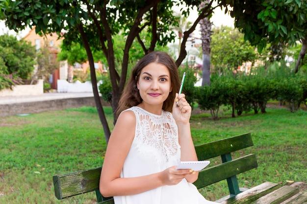 Een mooie vrouw die een notitieboekje en een pen vasthoudt heeft een idee a