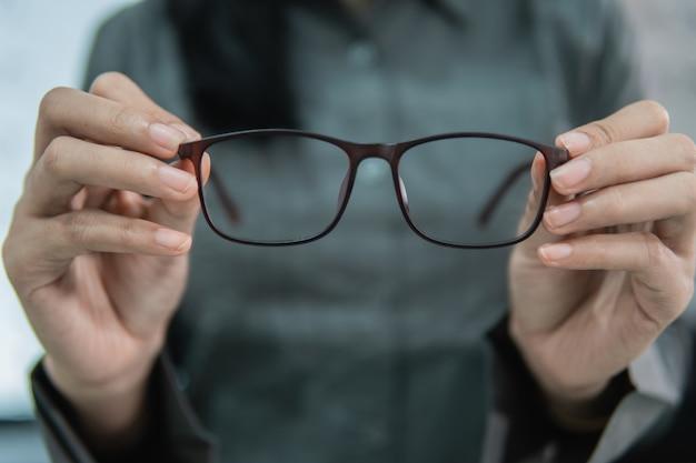 Een mooie vrouw die een steekproef van glazen in een oogkliniek houdt tegen de achtergrond van een lenzenvloeistofvenster