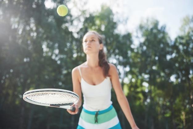 Een mooie vrouw die een tennisbaan in sportkleding draagt op de baan.