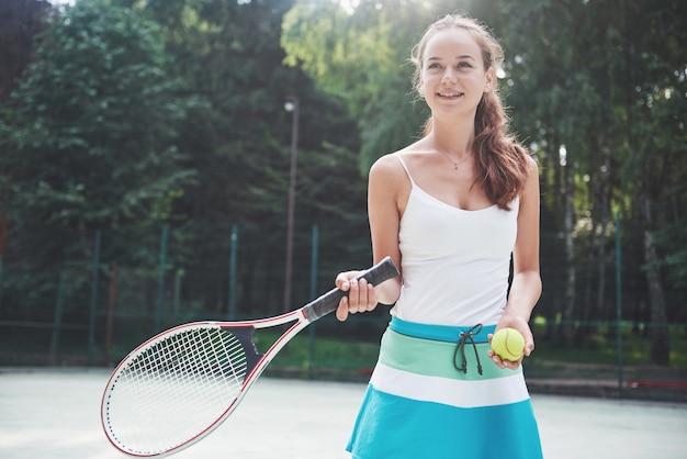 Een mooie vrouw die een tennisbal van sportkleding draagt.