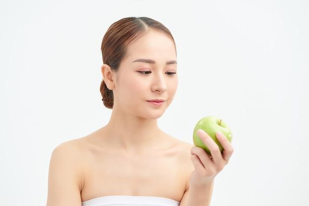 Een mooie vrouw die een verse groene appel houdt om te eten