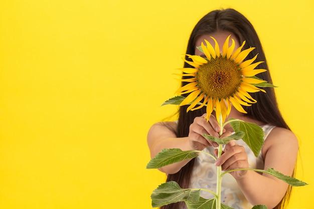 Een mooie vrouw die een zonnebloem op een gele achtergrond houdt.
